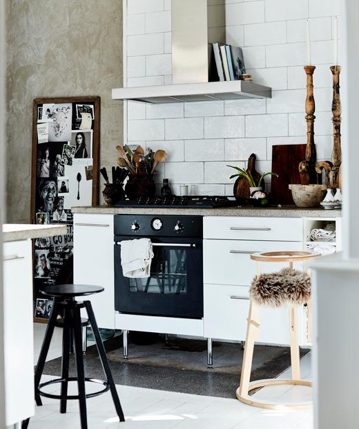 白色廚房裝有抽油煙機、白色瓷磚牆和木製配件。
