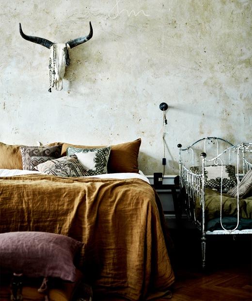 床上鋪有鐵銹色床單,旁邊放有白色的金屬嬰兒床,牆上有個動物頭骨裝飾。
