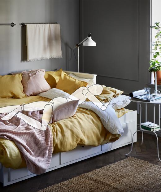 床上鋪滿枕頭和布藝產品,虛擬人形木偶擁著枕頭俯睡。