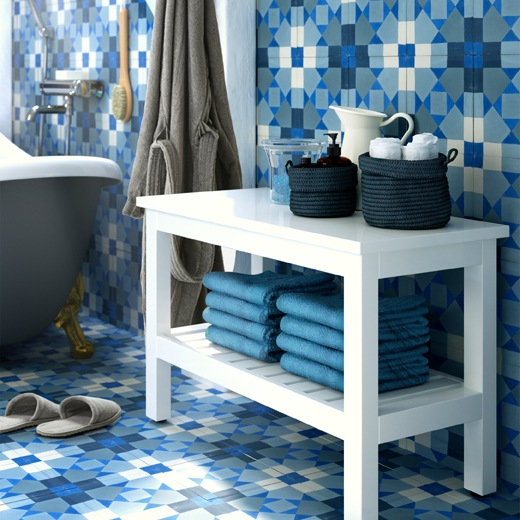 A white bench with towels on a lower shelf and accessories on top, with blue tiled walls and floor.