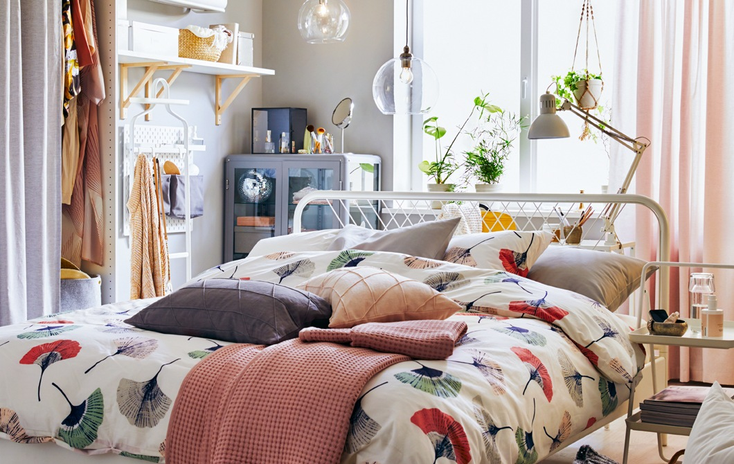 A bed dressed with floral bedding in the middle of a room with storage and shelves along the walls.