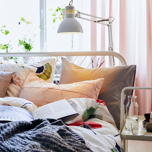 床上的書和枕頭上方掛著一盞白色檯燈。