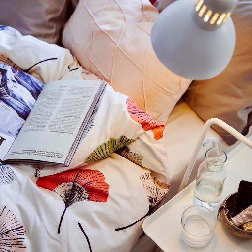 燈光照在花卉圖案床單、枕頭和書上,旁邊的白色小角几放有一杯水和水壺。
