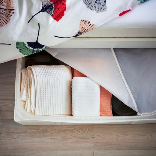 鋪上花卉圖案寢具的睡床下方,有一個拉鏈套貯物箱用作收納毛巾。