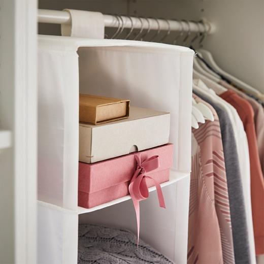 硬卡紙盒疊起放在懸掛式貯物袋內,旁邊是掛在衣桿上的衣服。