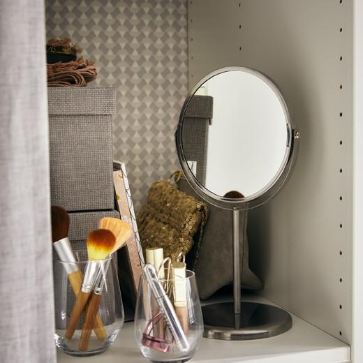 層板上有一塊小鏡子、裝在瓶內的化妝用具及貯物箱。
