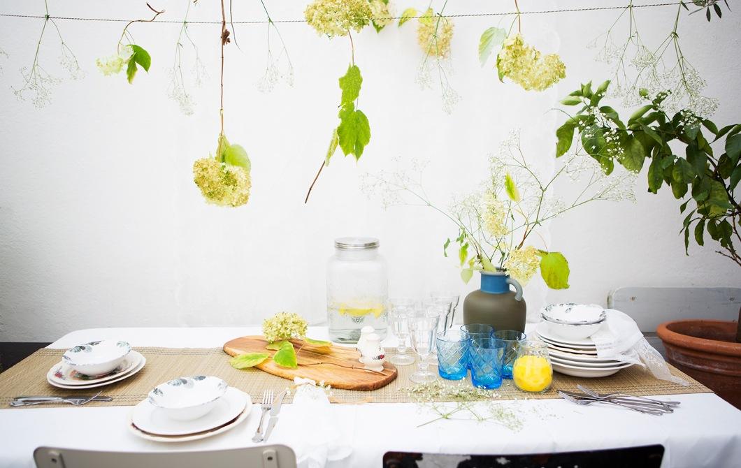 以花紋陶瓷碗碟、杯和一瓶鮮花布置的餐檯,上方亦掛有鮮花