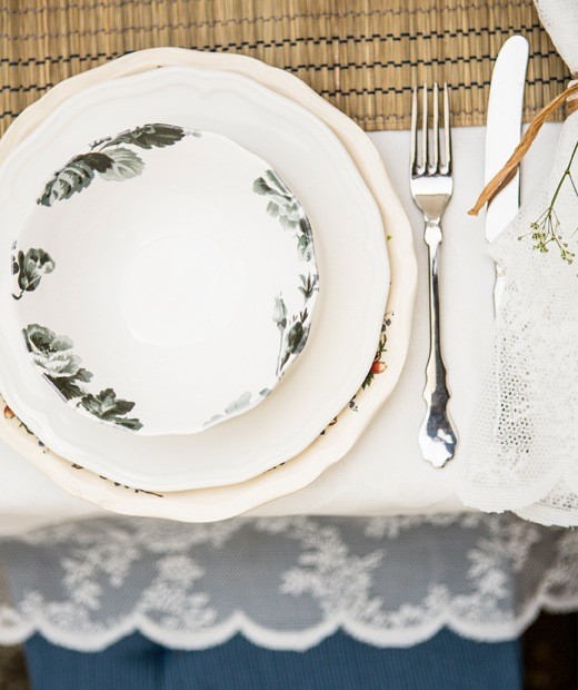 A floral plate stacked on two shaped plates, with cutlery and a white tablecloth.