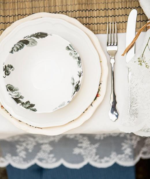 一隻花卉圖案餐碟疊在兩隻形狀特別的碟上,旁邊放有餐具和白色檯布。