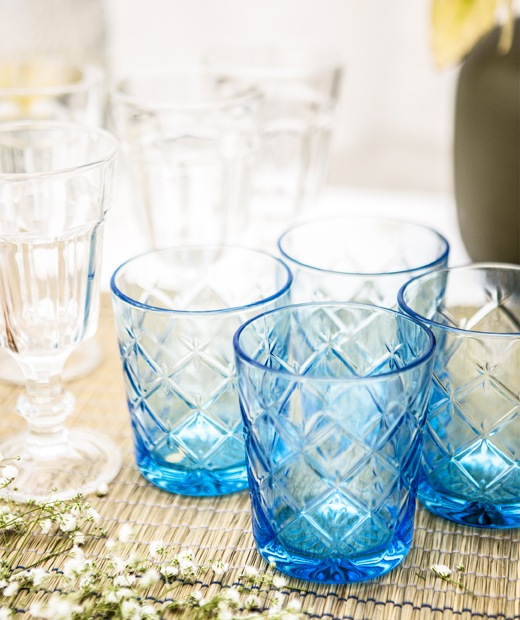 A group of blue cut glasses and clear wine glasses on a table runner.