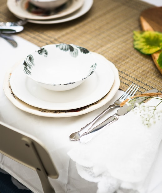 A stack of crockery and cutlery set on a seagrass table runner and white table cloth.