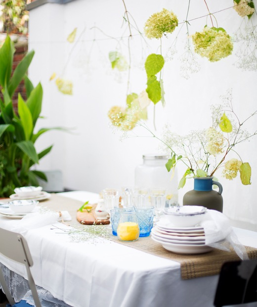 A table setting with stacked plates, glasses and a vase of flowers, with flowers hanging on string above.