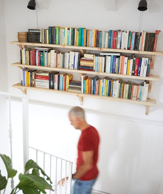 Three shelves of books on a white wall above a staircase.