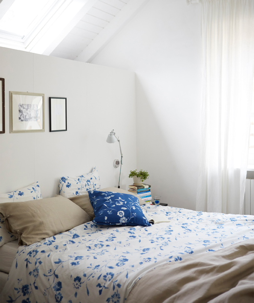 A white bedroom with blue and white floral bedding and a skylight.
