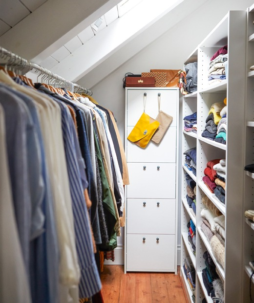 Clothes in a narrow storage area with drawers, shelves and rails.