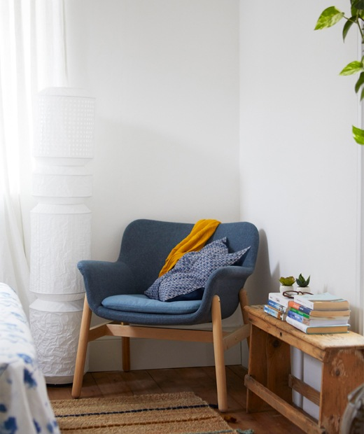 A blue armchair in the corner of a white room and a floorlamp with a paper shade.
