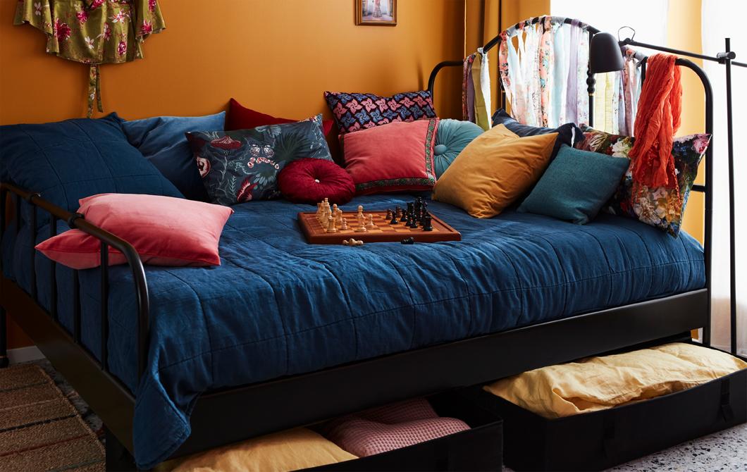 色彩繽紛、整齊鋪好的大床放有大量咕𠱸和一盤棋,床單放在床底的貯物箱。