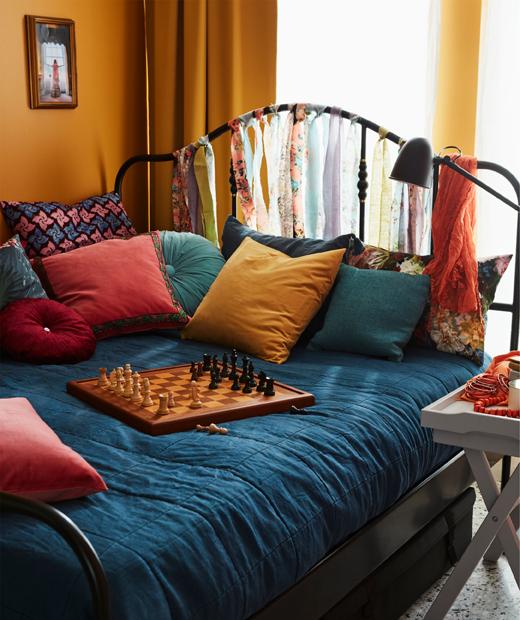 色彩繽紛、整齊鋪好的大床上放有咕𠱸和一盤棋,床邊的托盤几放了小食。