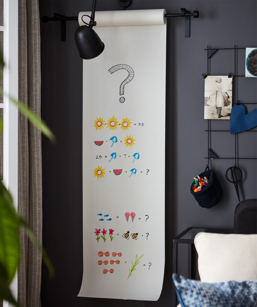 Corner of a room with a wall-mounted drawing-paper roll, a length of paper out with colourful, graphic maths problems.