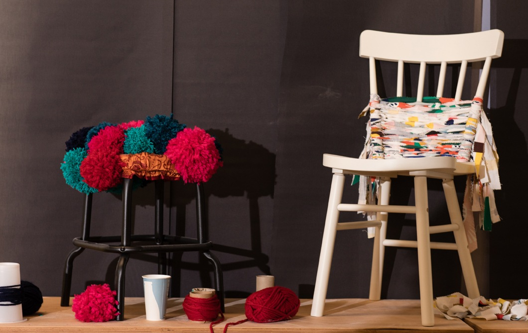 A black stool decorated with knitted shapes and a white chair decorated with scraps of fabric.