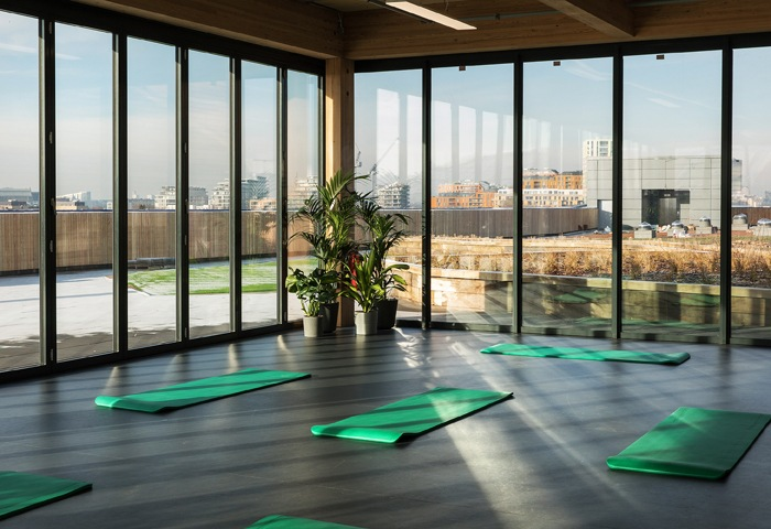 A room with yoga mats on the floor and full-height windows looking out over a city skyline.