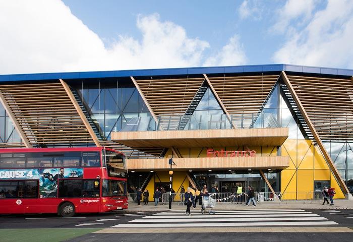 一輛紅色巴士駛過宜家家居倫敦格林威治新店門口,門面以木材及玻璃建成。