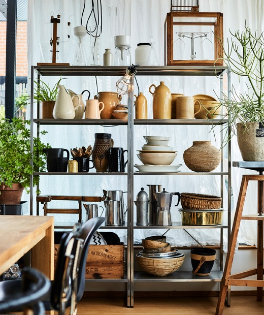 Ceramics and kitchenware displayed on tall metal shelving units.