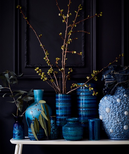 A collection of blue vases on a white bench.