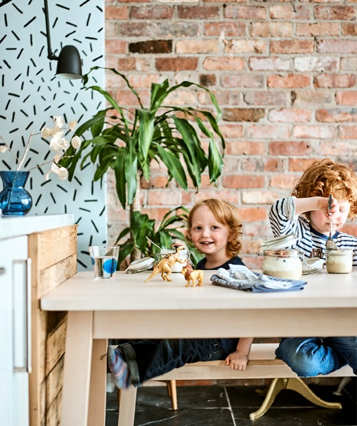Two children sit at a light wooden table with breakfast and toys, in front of a red brick wall.