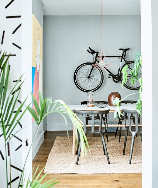 A dining area with table and chairs, plants and a bike hanging on the wall.
