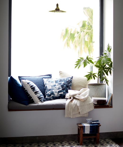 Cushions and a plant in a window seat.