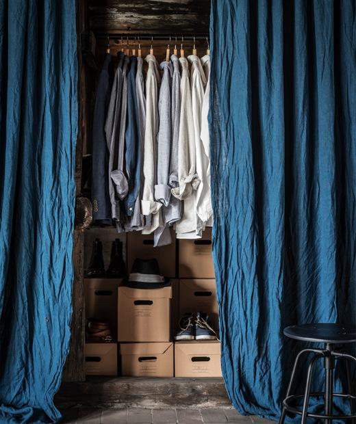 以藍色窗簾遮住背後的裇衫及鞋盒。