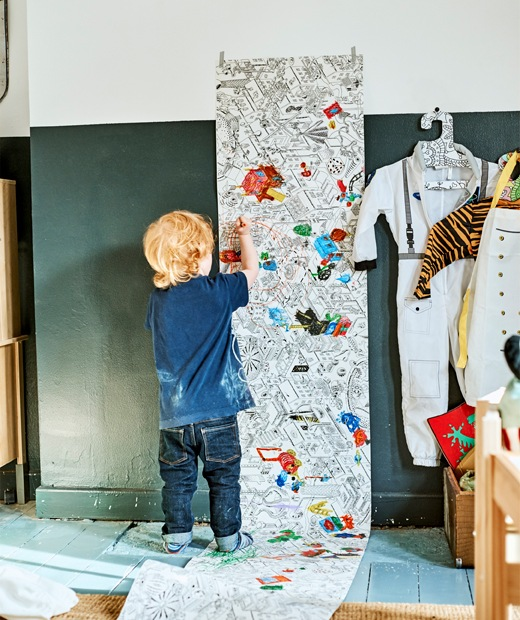 A child colouring in an illustrated roll of paper attached to the wall.