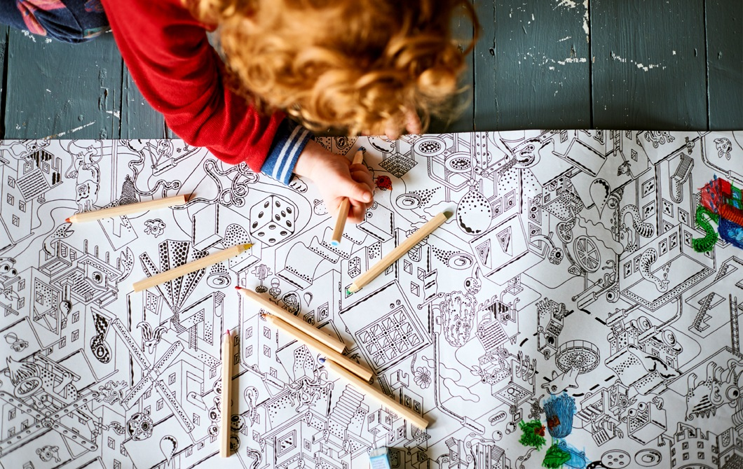 A child colouring in an illustrated sheet of paper on a painted wooden floor.