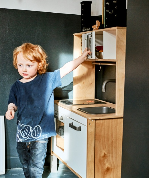 A child playing with a toy kitchen.