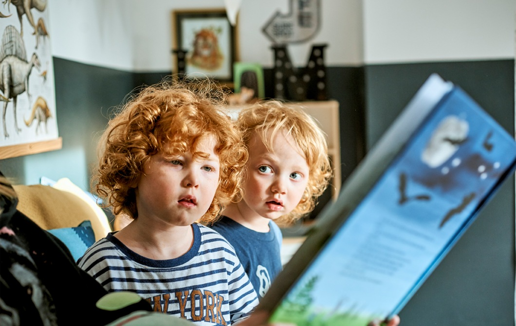 Two children being read to from a blue story book.
