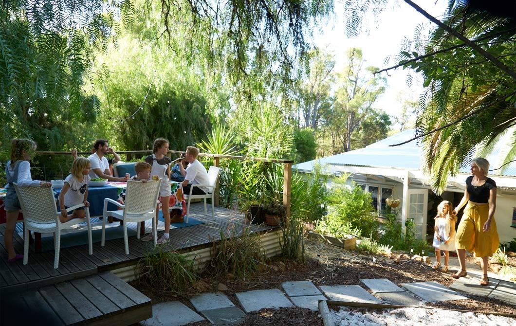 在花園的平台上,一群人坐在餐檯旁,四周種滿植物和鋪有石路面。