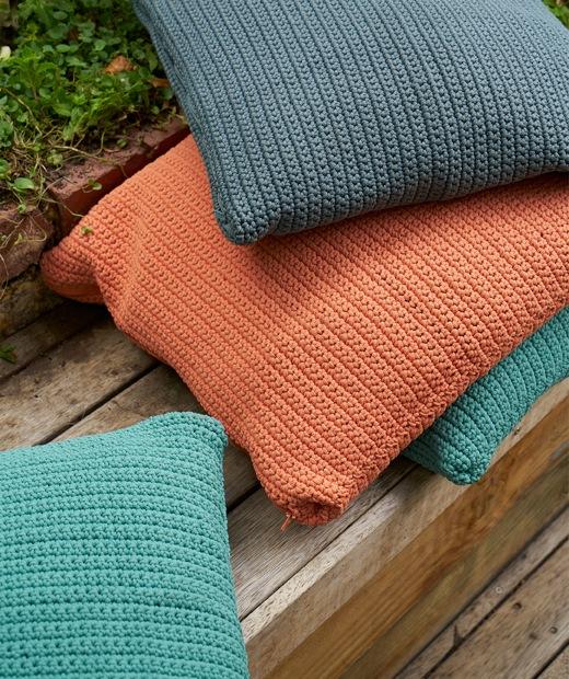 幾個橙色、藍色和藍綠色咕𠱸堆在戶外木地板平台上。