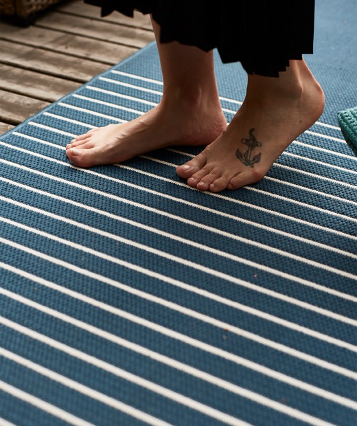 有個人赤腳踏在藍白色條紋地氈上。