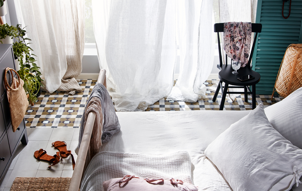 Bedroom with open, full-length windows with sheer curtains in front, seemingly swaying in an incoming breeze.