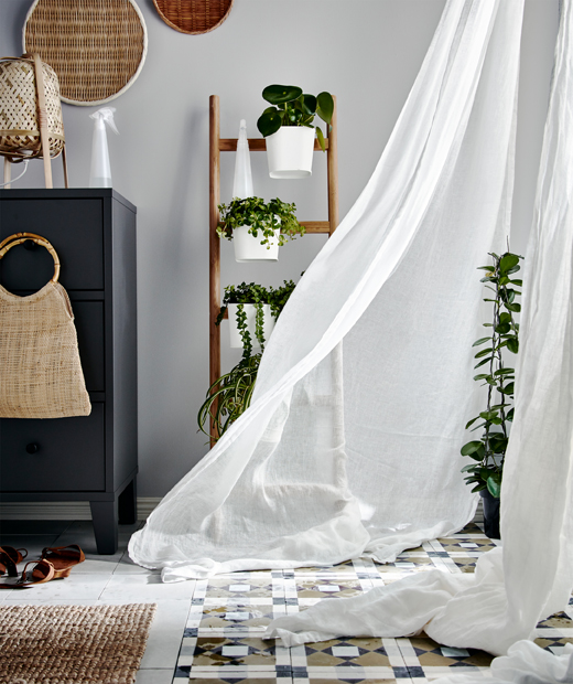 Corner of a room, plants next to full-length windows with sheer curtains in front, billowing from an incoming gust of wind.