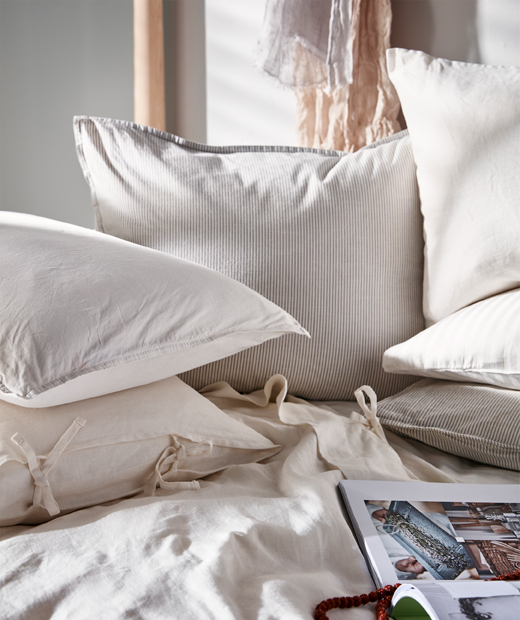 Sunlit bedscape laden with pillows and cushions in light-coloured textiles, an open book lying on the duvet.