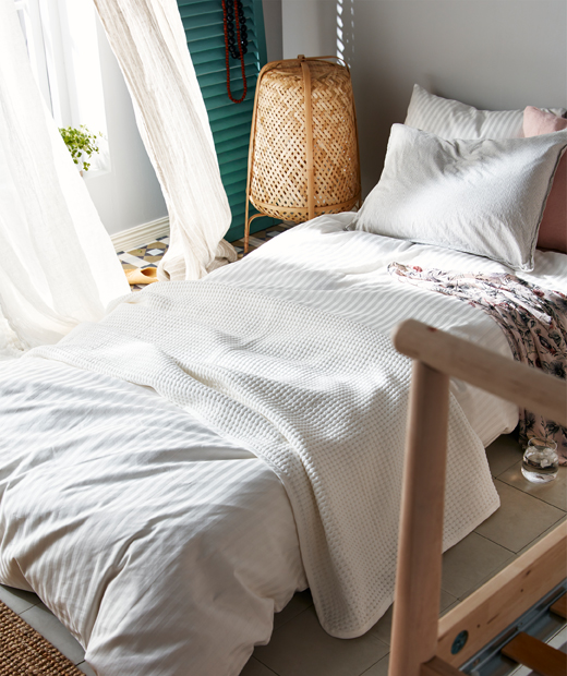 Mattress made for sleep on the floor next to open windows, the corner of a naked bedframe hinting at a temporary arrangement.