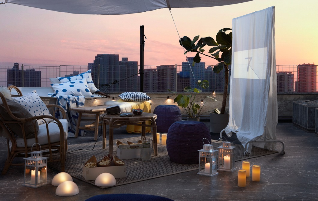 Rooftop, outdoor arrangement of seating, LED lighting and textiles at nightfall. A makeshift screen with film about to begin.