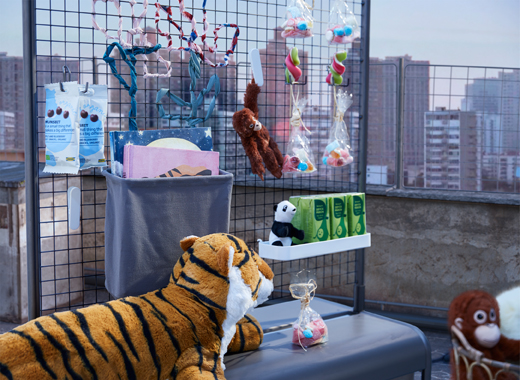 A makeshift refreshment stand with snacks and drinks, placed on a daytime rooftop and guarded by a fierce tiger.