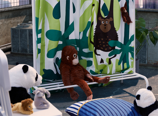 A curtained drama stage constructed from textile hung on a clothes rack, surrounded a star cast of DJUNGELSKOG soft toys.