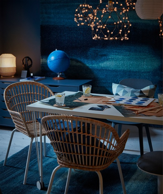 Table with drinks and star maps, wicker-style chairs, LED lighting above and SÖNDERÖD rugs both on the floor and wall.