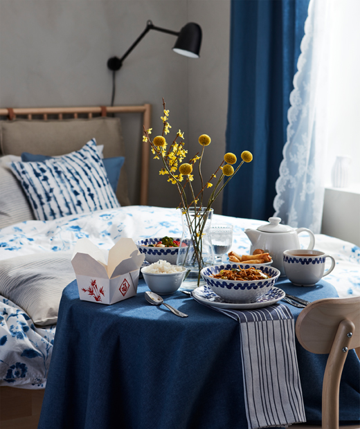 Cared-for dinner-for-one setting with oriental-style, multi-bowl meal on a small round table next to a bed.