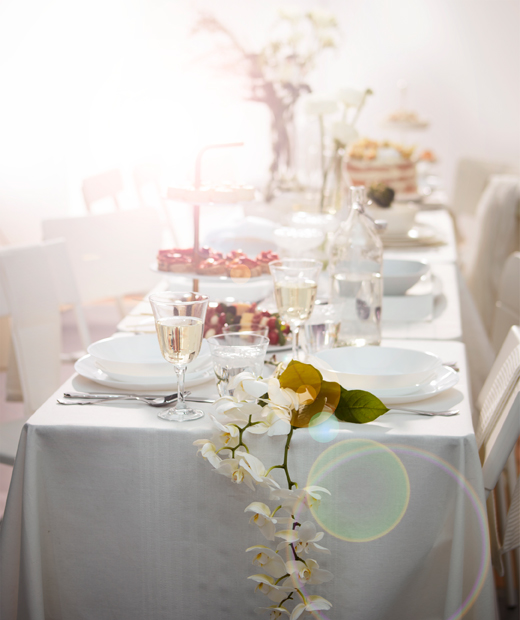 Long table set for dessert in romantic, lavish way in all white chairs, tables and textiles, with various floral decorations.