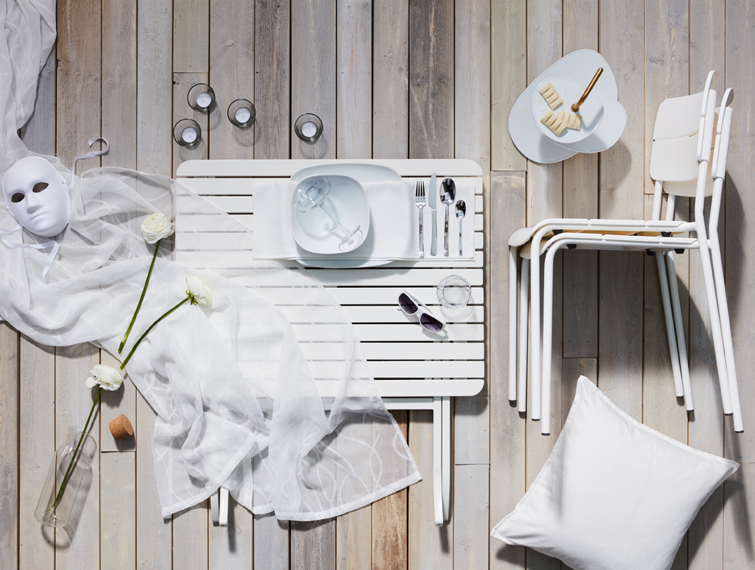 Layout of a dinner kit in all white, with modern, clean lines and matching textiles; tableware including serving stand.
